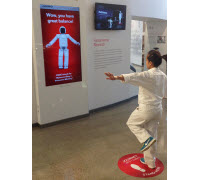 A Honda associate interacts with ASIMO at the Honda Heritage Center