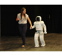 ASIMO shows the audience it can walk hand in hand with a person.