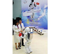 ASIMO introduces Ms Nimet Çubukçu, the Turkish Education Minister, to the stage and presents her with the flags of the two countries.